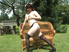 This sexy redheaded calm whore is looking worthy in her lingerie and this chick teases us during sitting on her wicker chair in the backyard. She rubs her pussy and plays with her saggy, typical boobs. Her light skin is glorious.