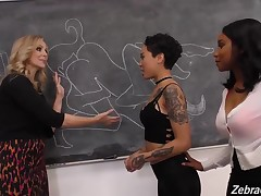 Lusty lesbian babes are having an interracial threesome in the classroom, while no one is watching