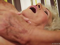 A very furry granny stimulates her old clit